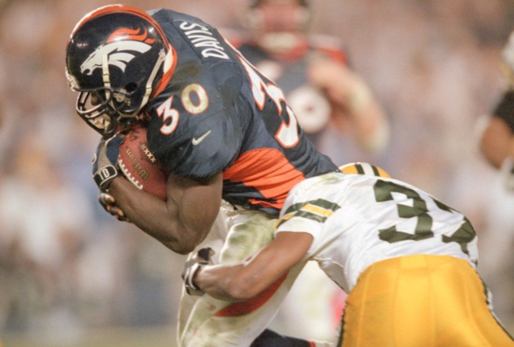 Terrell Davis of the Denver Broncos looks to break the tackle of Tyrone Williams of the Green Bay Packers during Super Bowl XXXII.