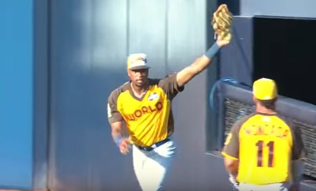Eloy Jimenez holds his glove in the air after making a catch