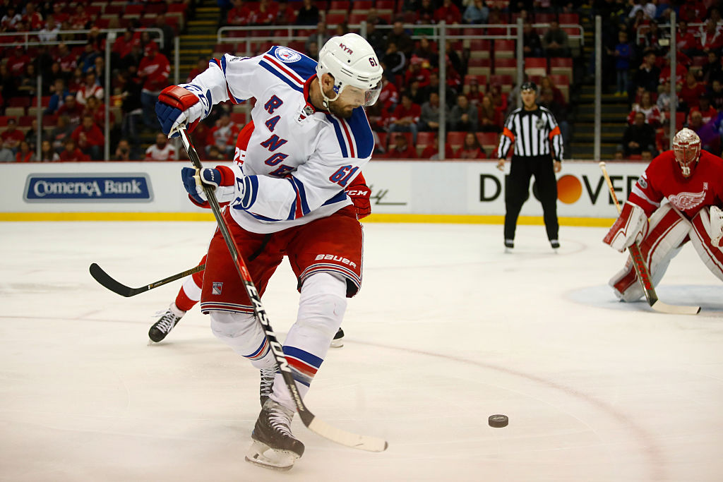 Rick Nash of the New York Rangers tries to control the puck in front of Mike Green of the Detroit Red Wings.