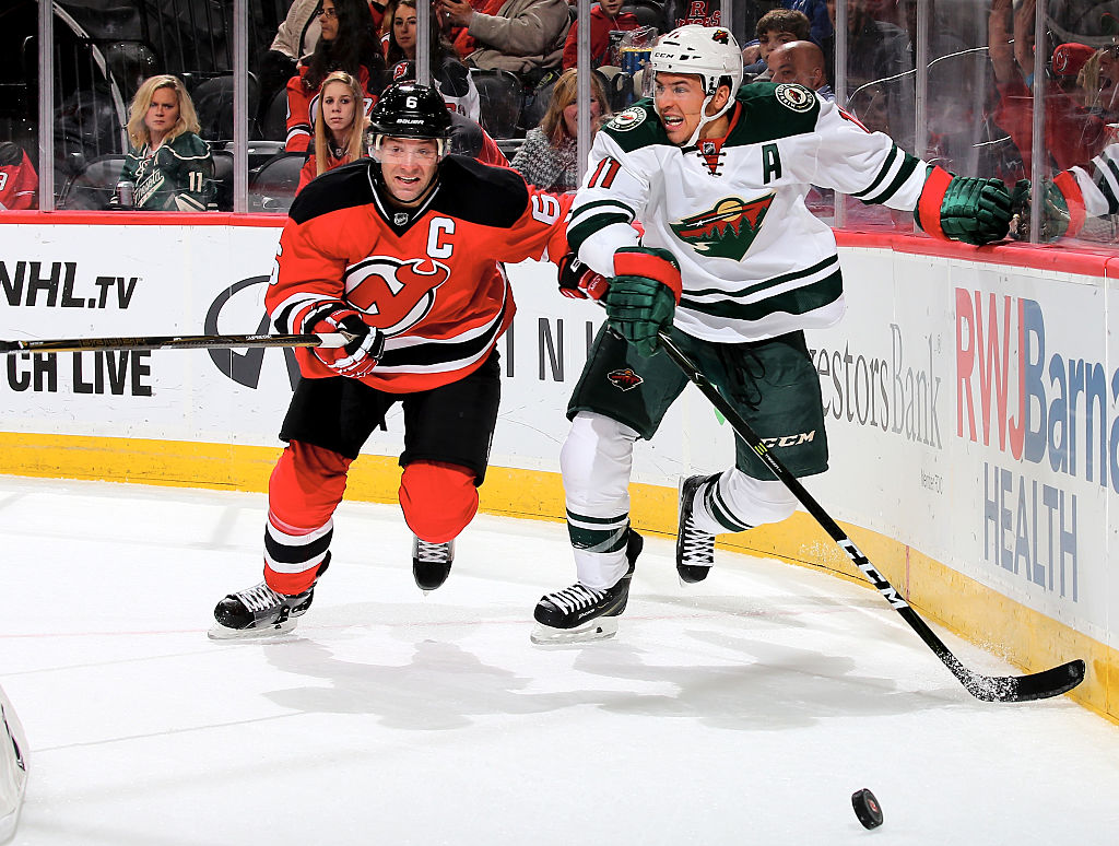 Zach Parise of the Minnesota Wild takes the puck as Andy Greene of the New Jersey Devils defends.