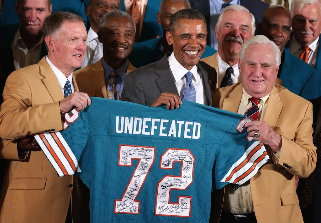 Former President Barack Obama poses for photos with the 1972 Miami Dolphins including head coach Don Shula, quarterback Bob Griese, and running back Larry Csonka.