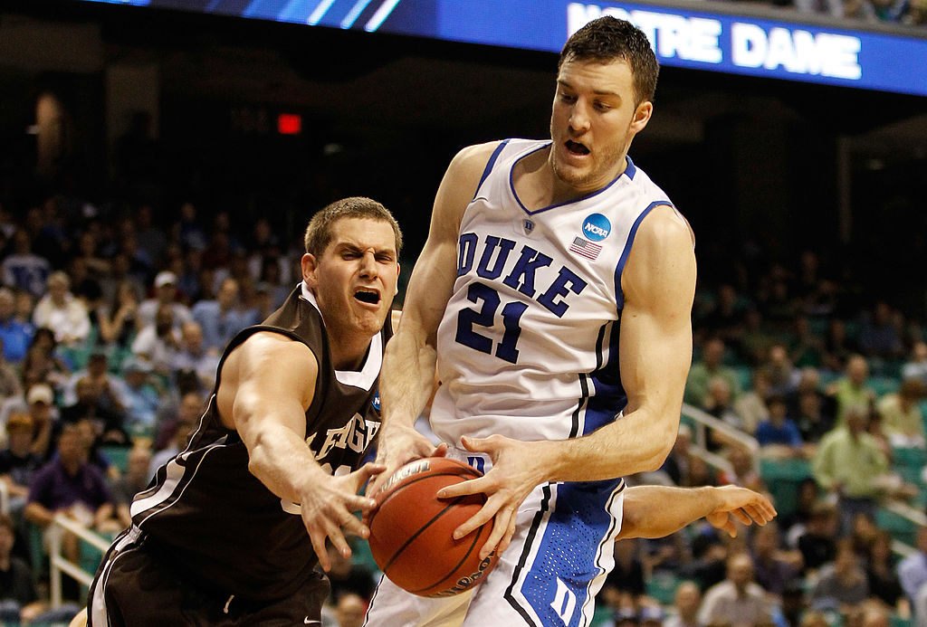 Miles Plumlee of the Duke Blue Devils grabs the ball as Justin Maneri of the Lehigh Mountain Hawks attempts to grab it.