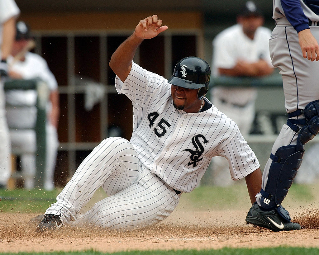 Carlos Lee of the Chicago White Sox slides across home plate on a double by teammate Juan Uribe.