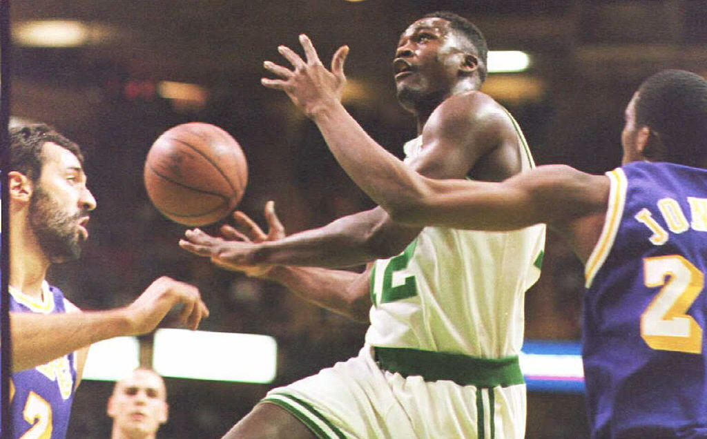 Dominique Wilkins of the Boston Celtics drives to the basket past Vlade Divac and Eddie Jones of the Los Angeles Lakers.