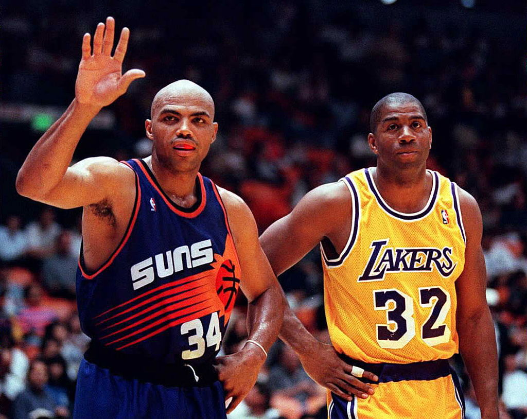 Charles Barkley of the Phoenix Suns waves to fans as Magic Johnson of the Los Angeles Lakers watches.