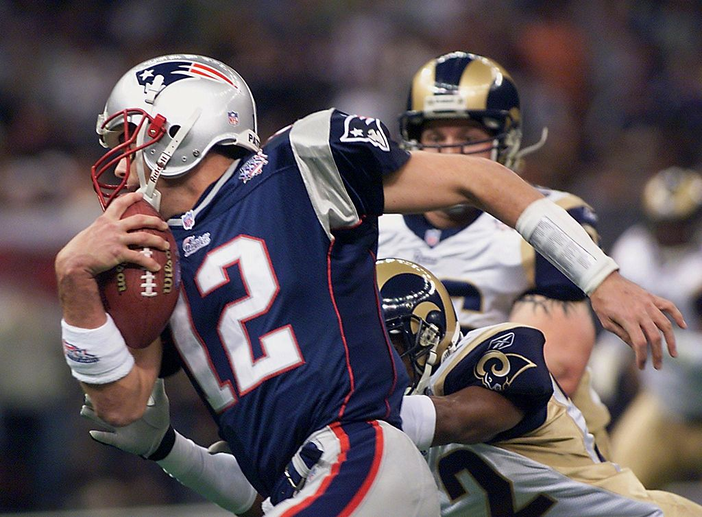New England Patriots quarterback Tom Brady tries to avoid being tackled during the first half of Super Bowl XXXVI.