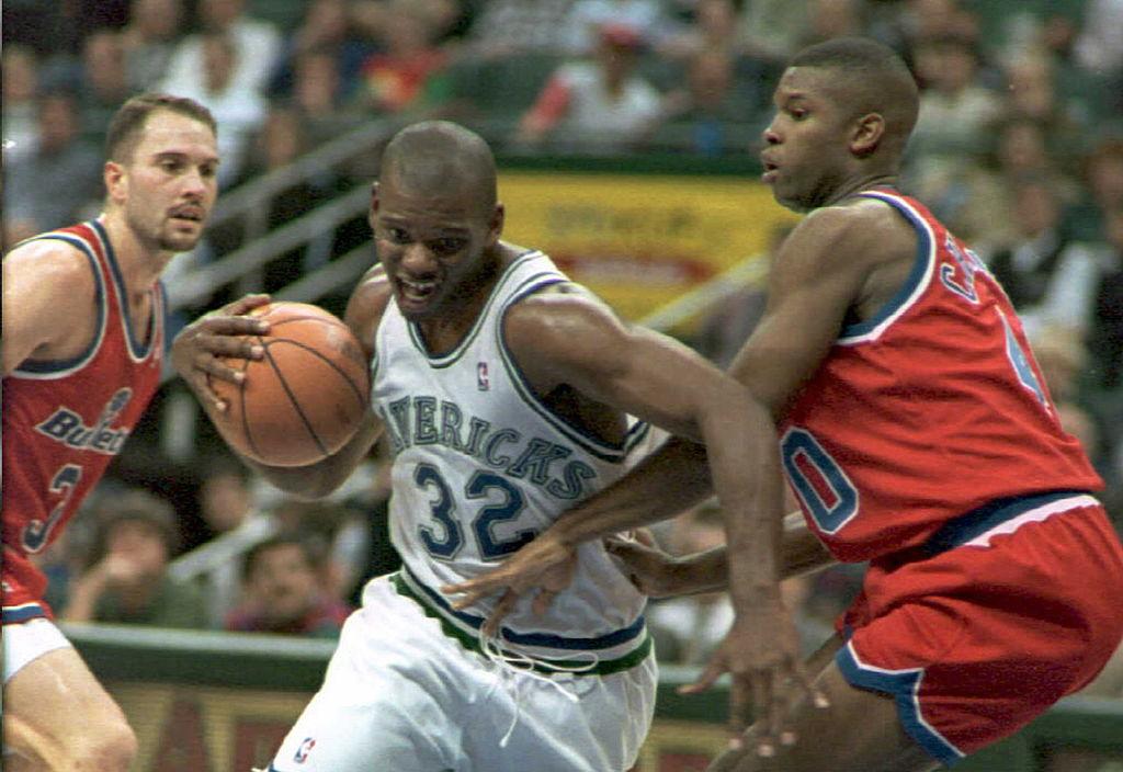 Jamal Mashburn of the Dallas Mavericks drives between Washington Bullets Rex Chapman and Calbert Cheaney.