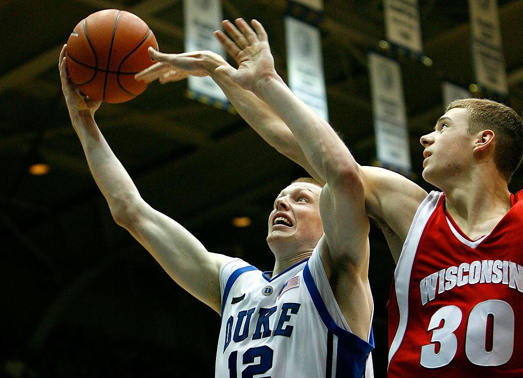 Kyle Singler of the Duke Blue Devils drives to the basket against Jon Leuer of the Wisconsin Badgers.