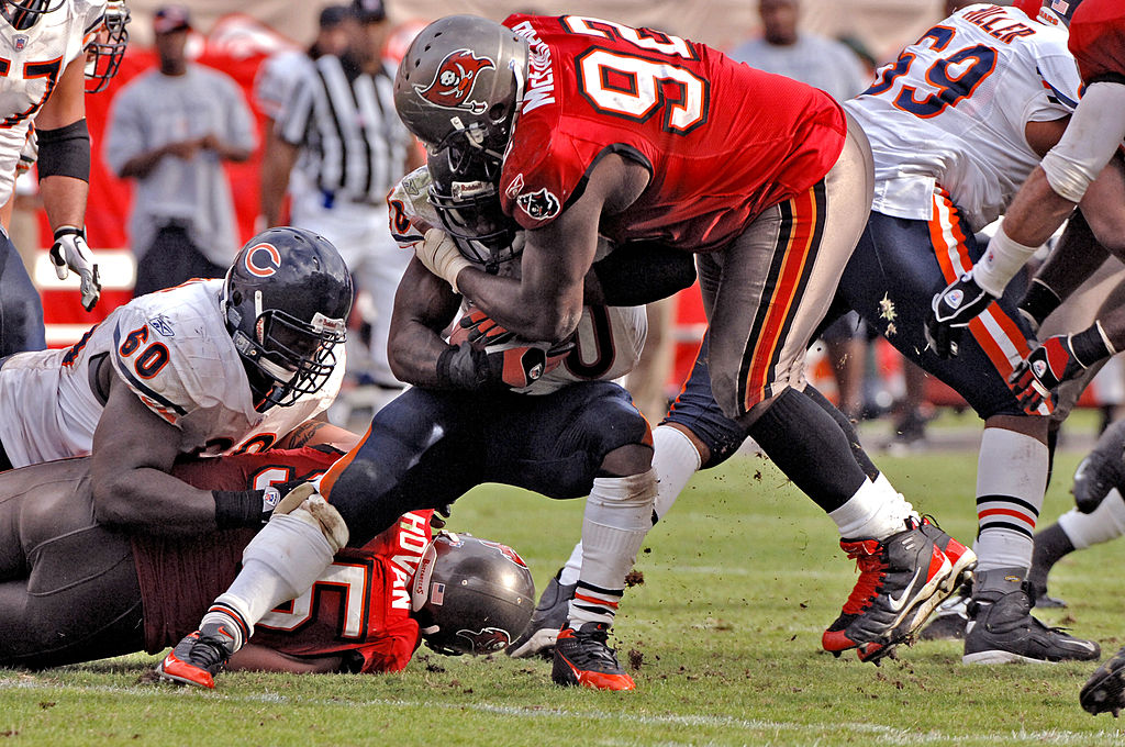 Anthony McFarland tackles Chicago Bears running back Thomas Jones.