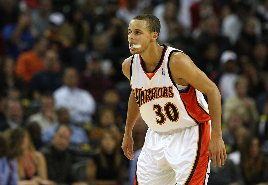 Stephen Curry bites on his mouthguard as he waits for a game to begin.