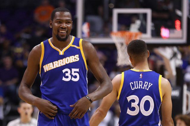 Kevin Durant and Stephen Curry laugh together and celebrate a play.