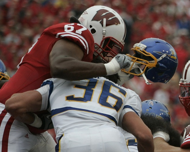 Wisconsin's Josh Oglesby rips the helmut off San Jose State's Vince Buhagiar.
