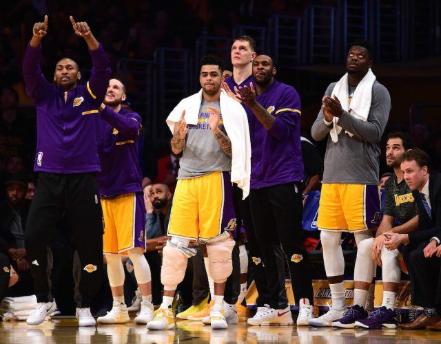 The Los Angeles Lakers applaud from the bench.