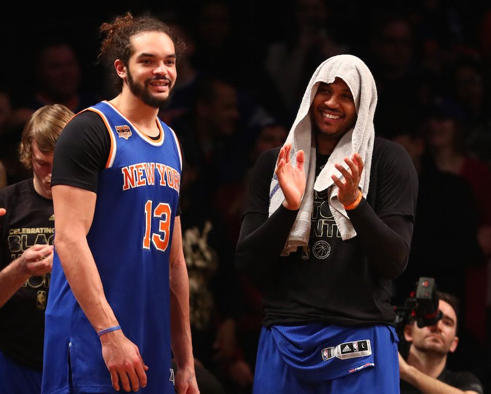 Joakim Noah and Carmelo Anthony smiles on the sideline.