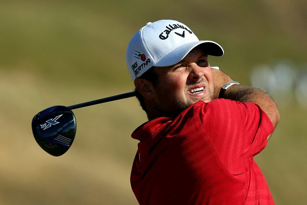 Patrick Reed squints into the sun as he swings.