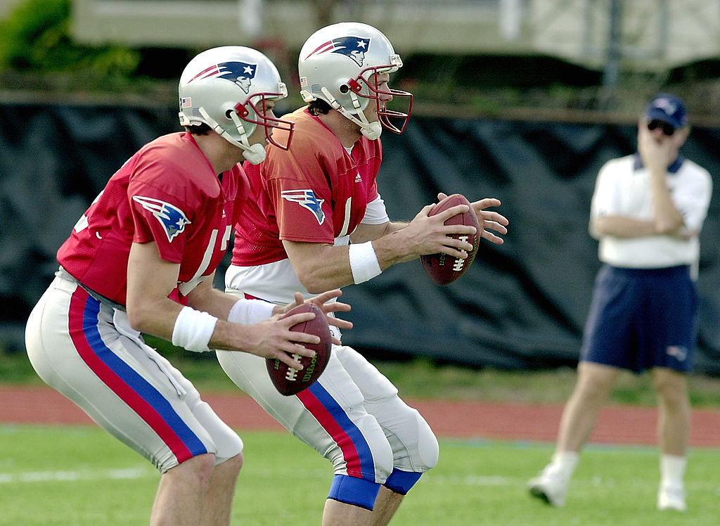 New England Patriots' quarterbacks Drew Bledsoe and Tom Brady run drills side-by-side. | Roberto Schmidt/AFP/Getty Images