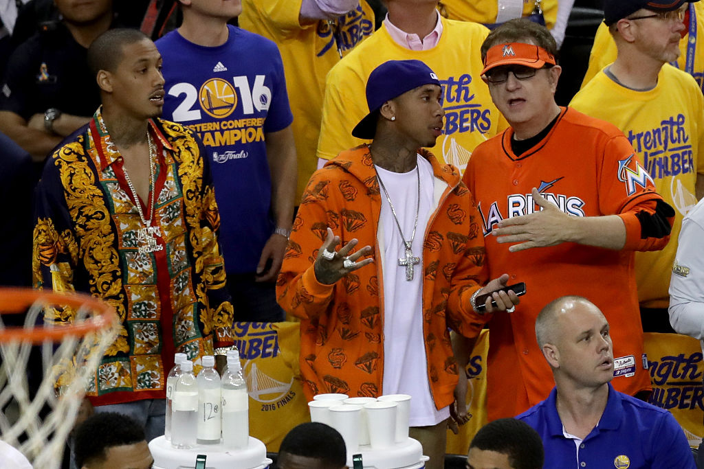 Rappers A.E and Tyga talk with Marlins Man Laurence Leavy during Game 5 of the 2016 NBA Finals.