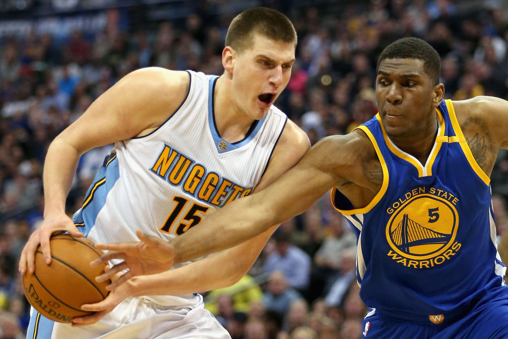 Nikola Jokic of the Denver Nuggets drives to the basket against Kevin Looney of the Golden State Warriors.