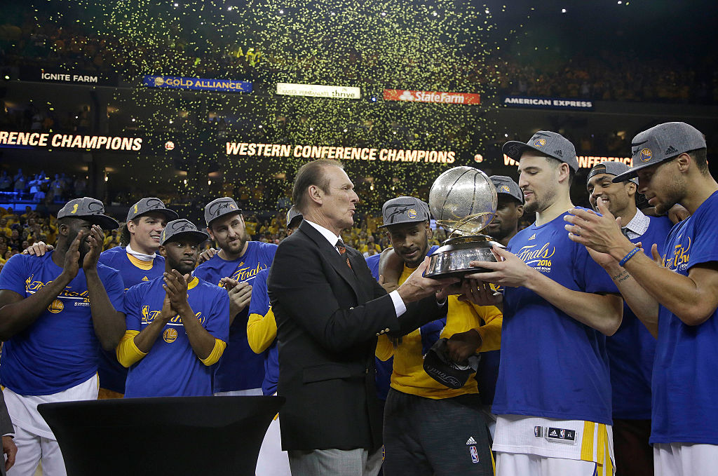 Klay Thompson #11 of the Golden State Warriors is presented the Western Conference Championship Trophy by former NBA player Rick Barry after defeating the Oklahoma City Thunder in Game Seven of the Western Conference Finals during the 2016 NBA Playoffs at ORACLE Arena on May 30, 2016 in Oakland, California. | Pool/Getty Images