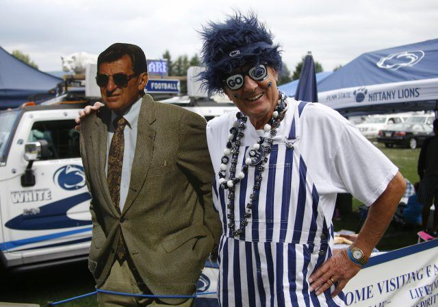A Penn State fan stands with a Joe Paterno cutout.