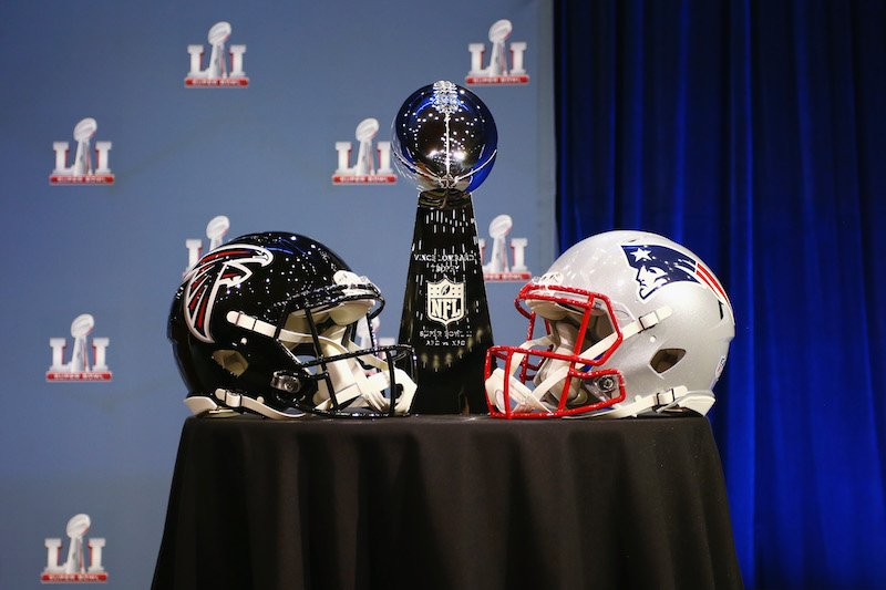 Falcons and patriots helmets rest on a stage.