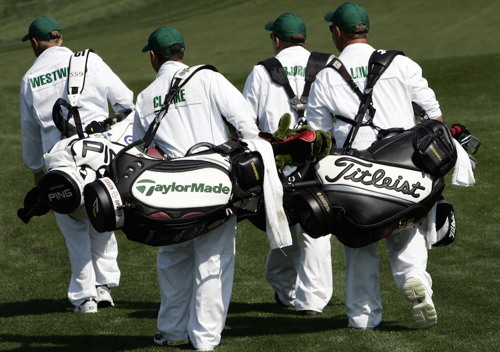 Caddies for golfers participating in the 2005 Masters walk down the first fairway.