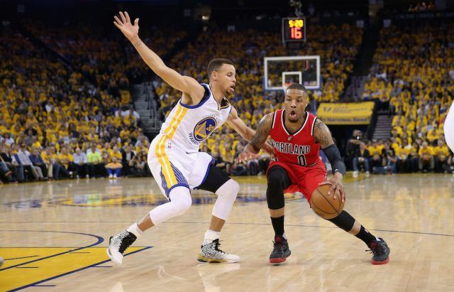 Damian Lillard (R) drives on Stephen Curry.