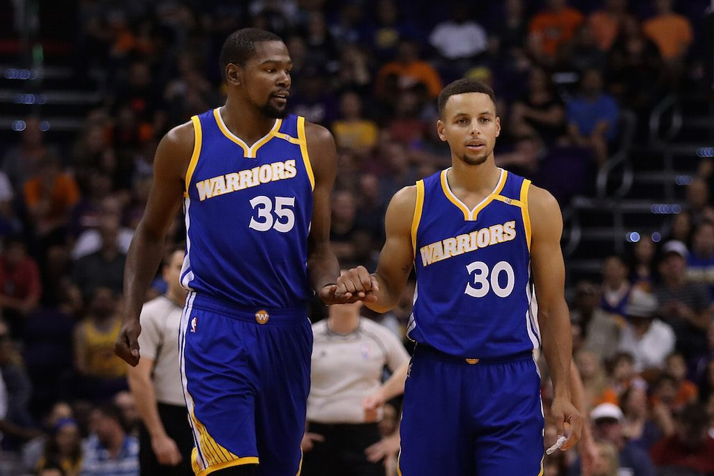 Kevin Durant and Stephen Curry chat on the court.