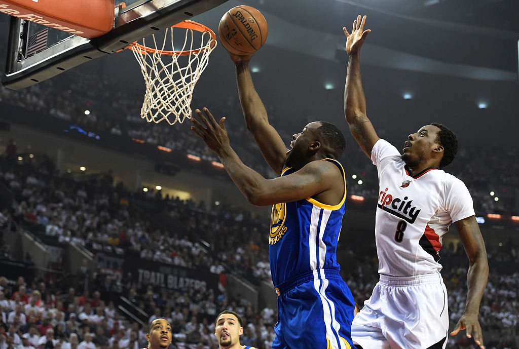 Draymond Green of the Golden State Warriors drive to the basket on Al-Farouq Aminu of the Portland Trail Blazers.