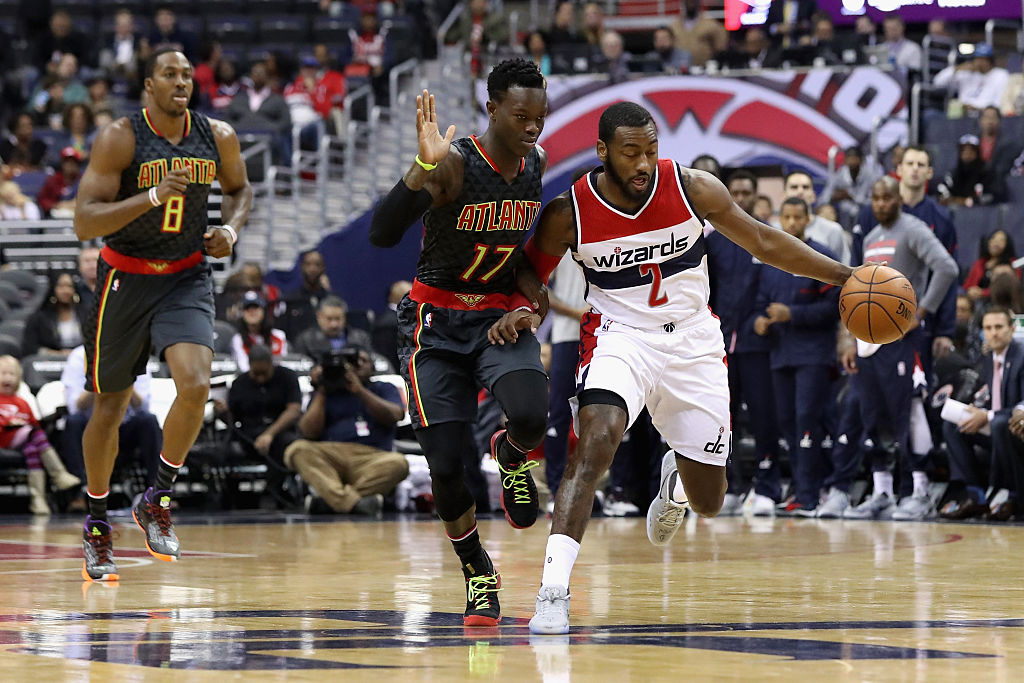 John Wall of the Washington Wizards moves the ball past Dennis Schroder of the Atlanta Hawks.