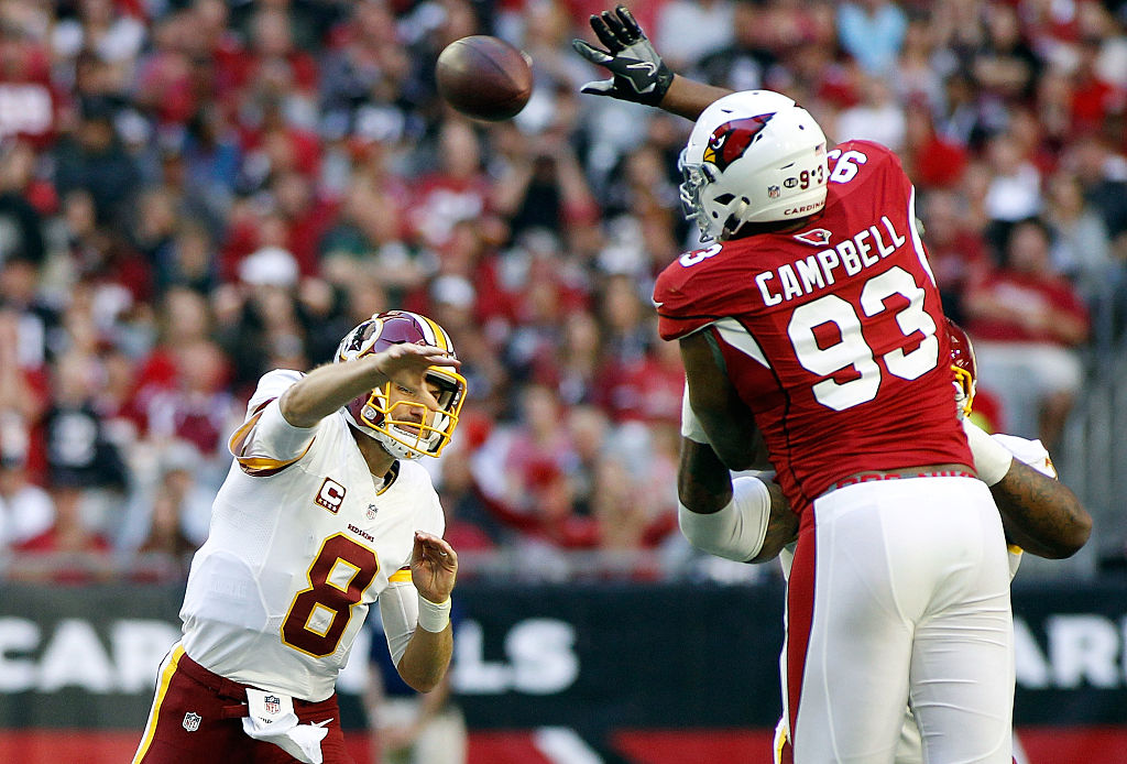 Calais Campbell of the Arizona Cardinals leaps to block the pass of quarterback Kirk Cousins of the Washington Redskins