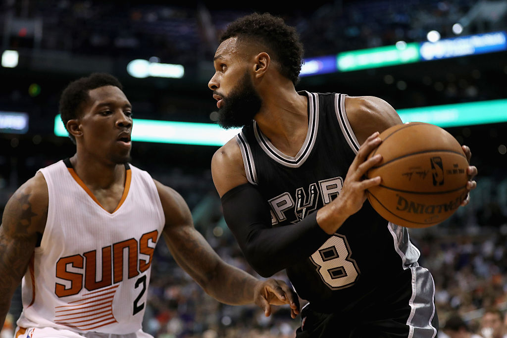Patty Mills of the San Antonio Spurs looks to pass around Eric Bledsoe of the Phoenix Suns.