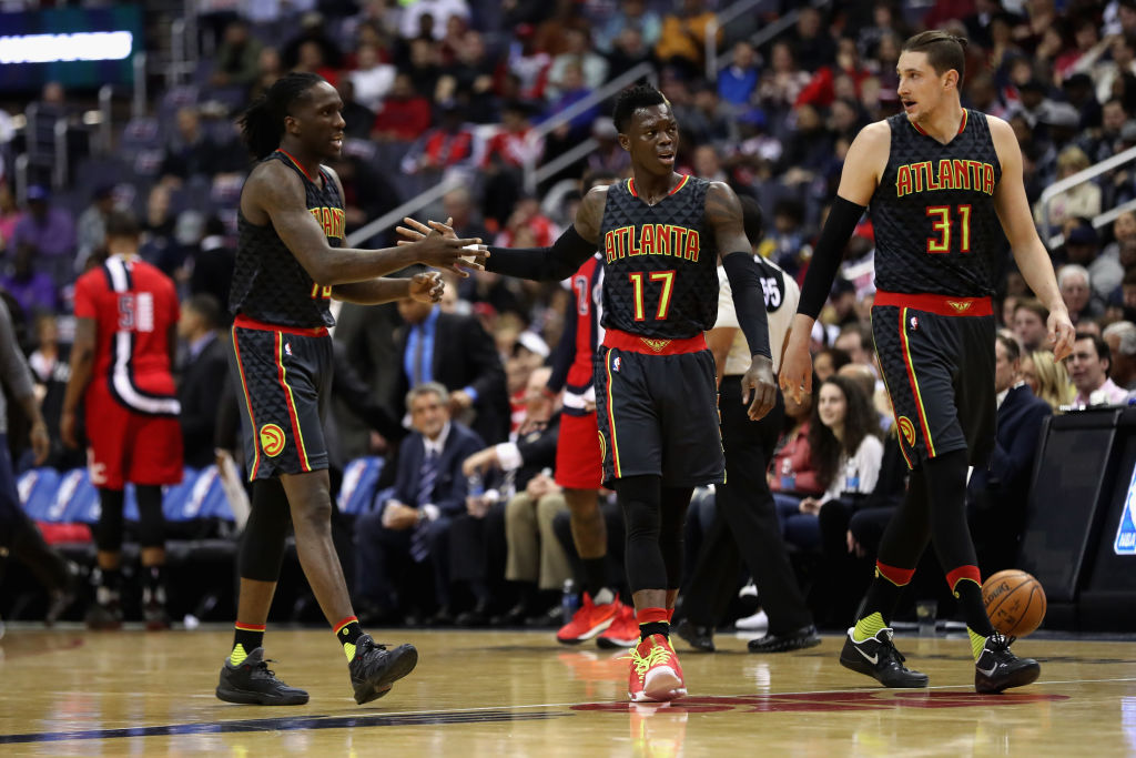 Taurean Prince, Dennis Schroder, and Mike Muscala of the Atlanta Hawks walk off the floor during a timeout.