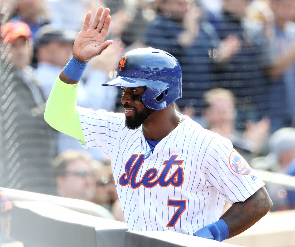 Jose Reyes goes for a high five as he walks into the dugout.