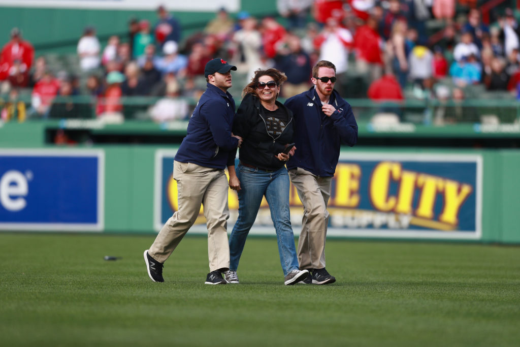 A fan is escorted from the field in the top of the ninth inning during the game between Boston Red Sox and the Pittsburgh Pirates.