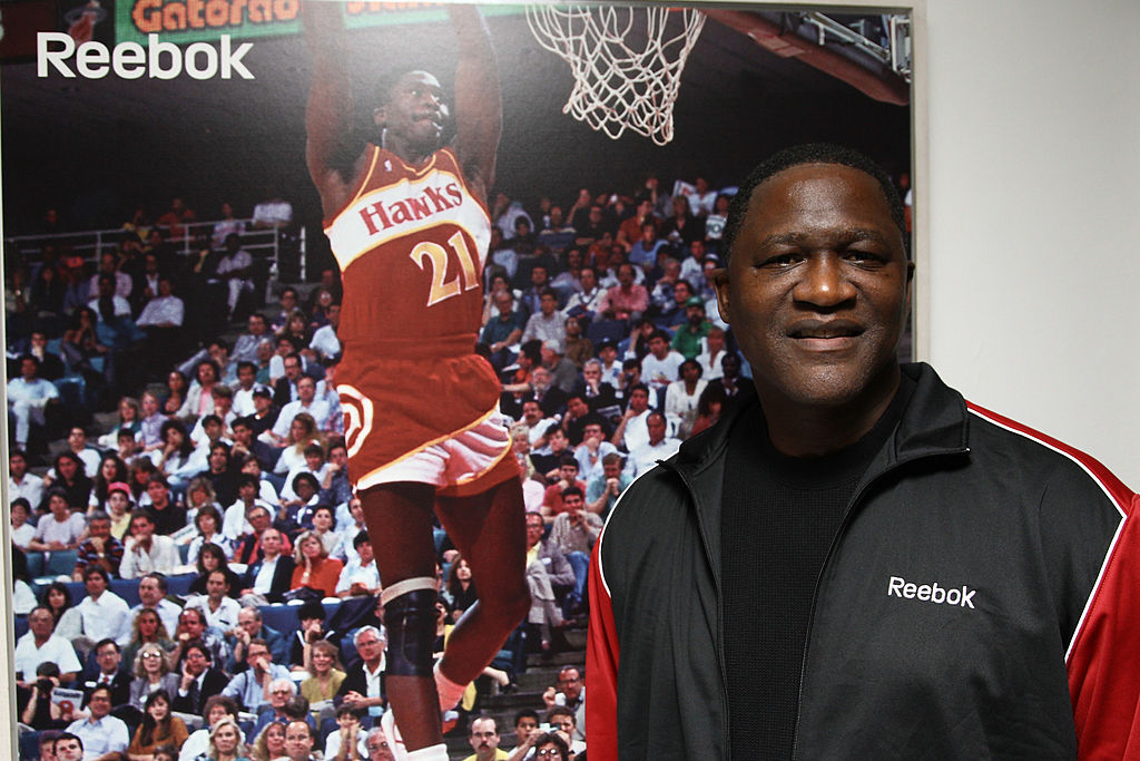 Former NBA player and Hall of Famer Dominique Wilkins poses next to his own poster.