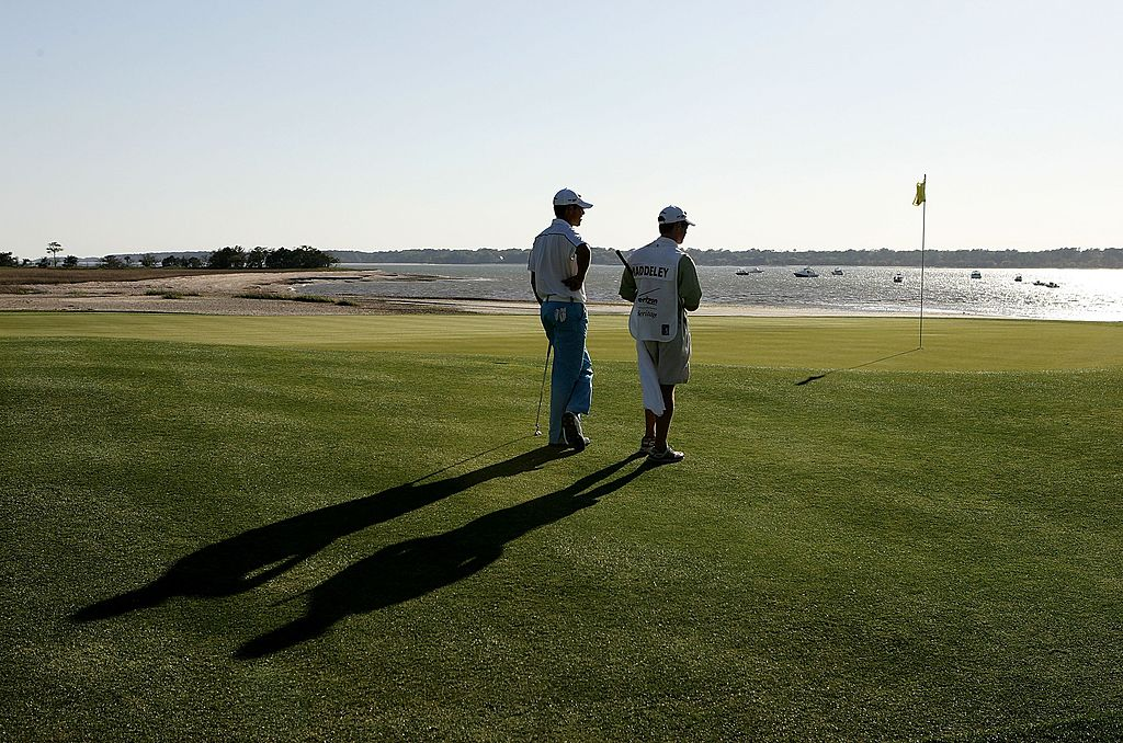 Aaron Baddeley of Australia and his caddie Kenny Harms watch on at the 18th hole during the third round.