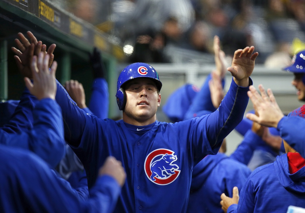 Anthony Rizzo high fives his teammates in the dugout.