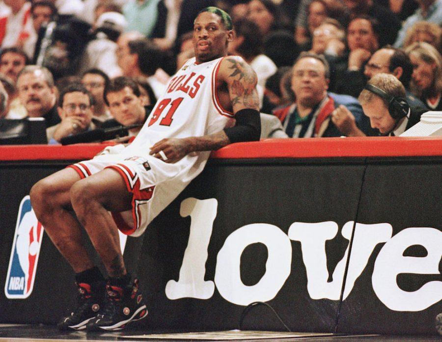 Dennis Rodman leans against the scorers table.