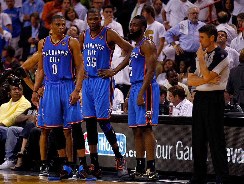 Russell Westbrook, Kevin Durant, and James Harden wait to be subbed in.