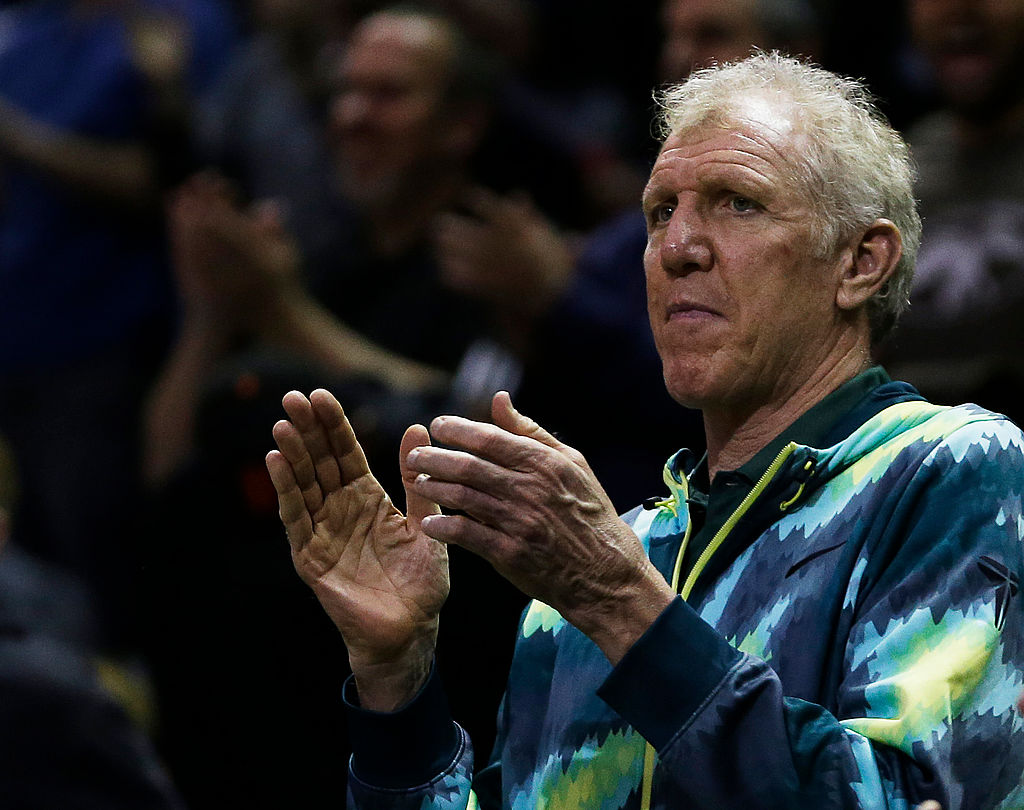 Bill Walton applauds during a basketball game.