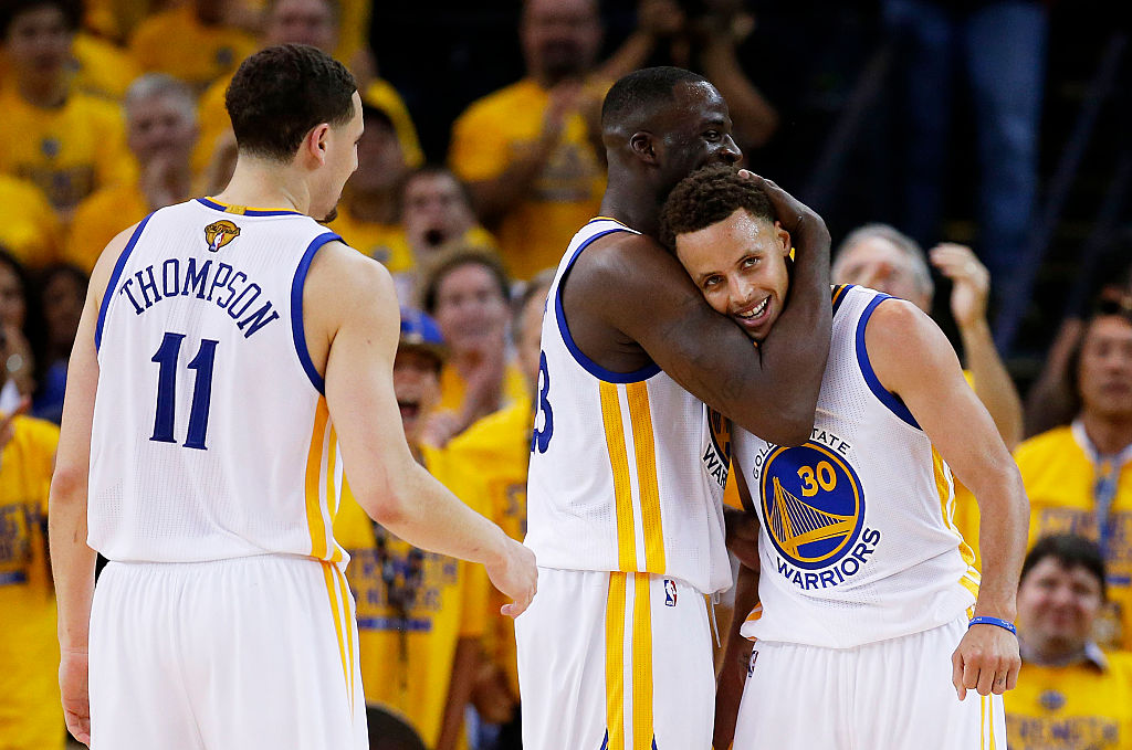 Stephen Curry, Klay Thompson, and Draymond Green celebrate a play in the 2015 NBA Finals.
