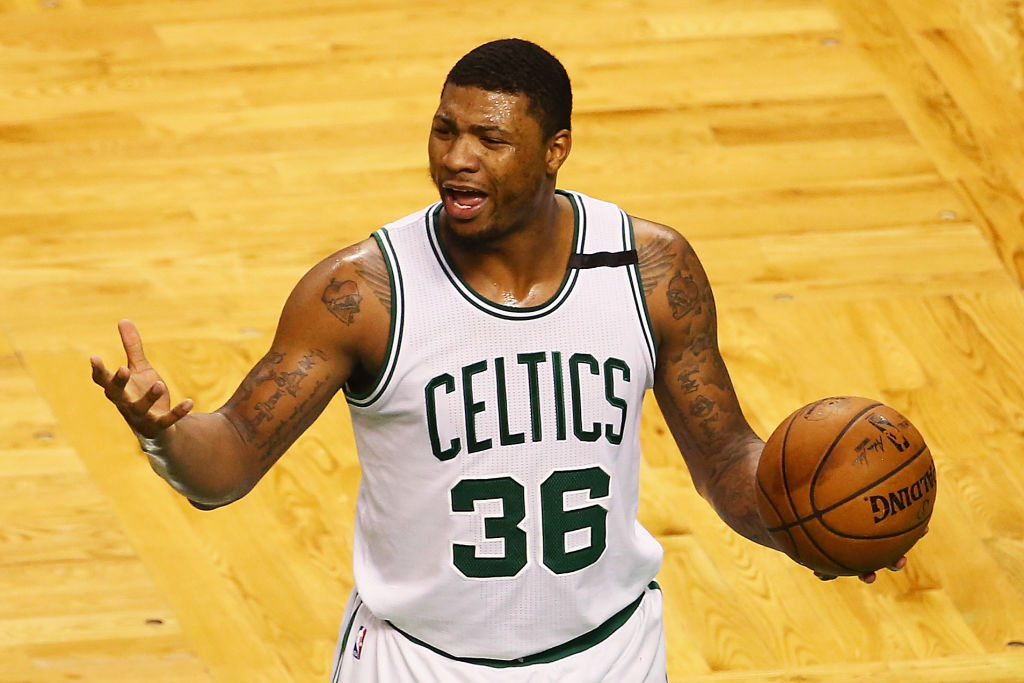 Marcus Smart gestures while holding the basketball ball.