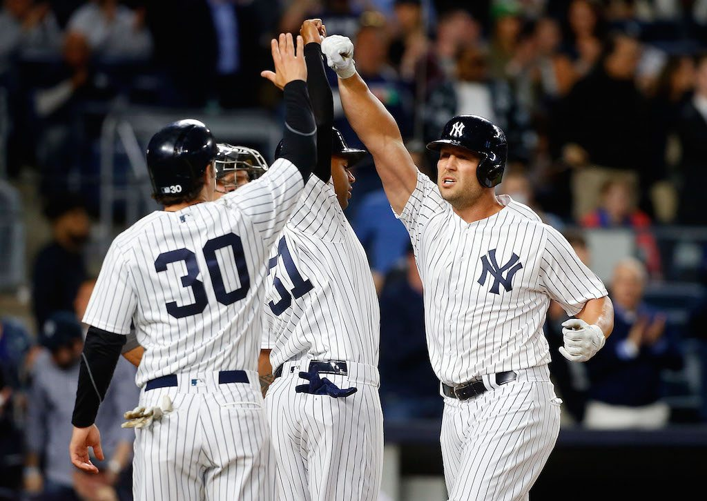 Matt Holliday of the New York Yankees celebrates his third-inning, three-run home run against the Chicago White Sox with teammates Aaron Hicks and Pete Kozma.