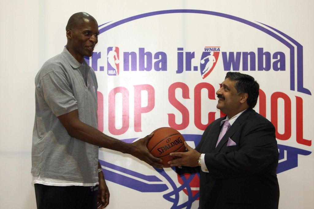 Robert Parish presents a basketball during a press conference.