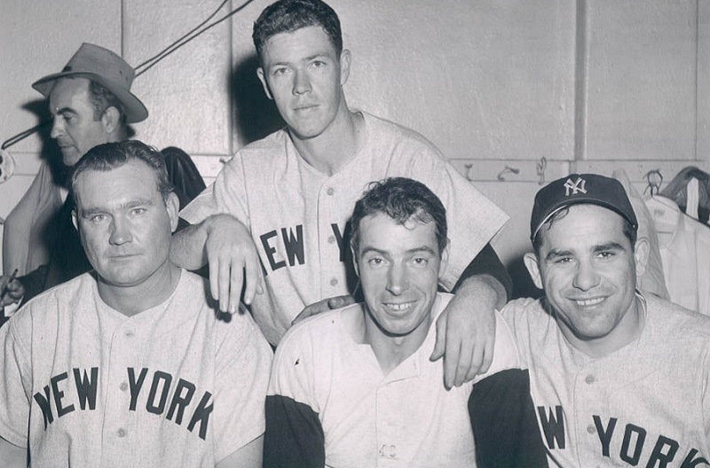 Shot of Joe DiMaggio, Yogi Berra and two other Yankees players in the clubhouse during the dynasty of the 1947–53.