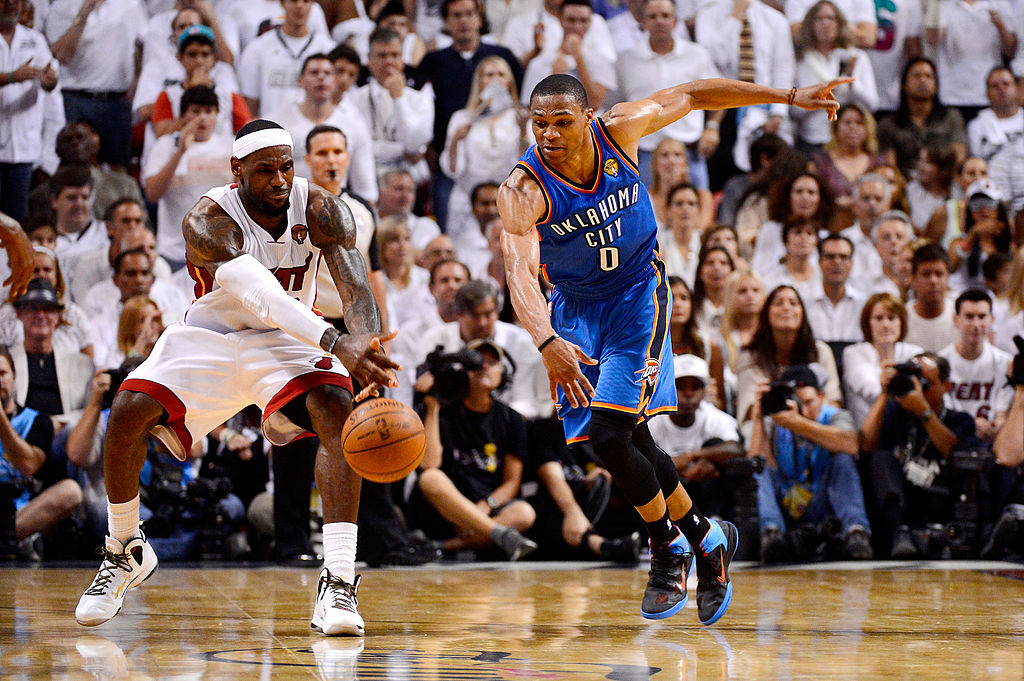 LeBron James grabs the ball in front of Russell Westbrook.