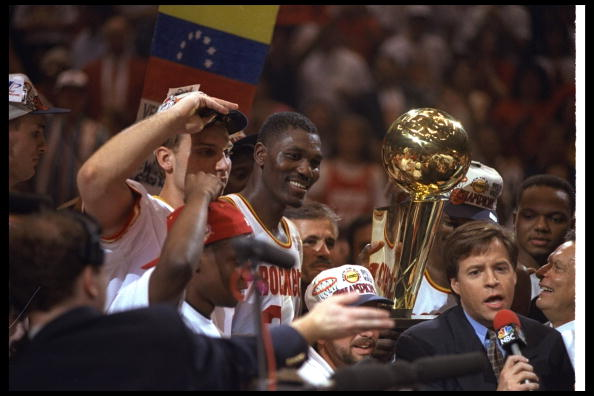 Hakeem Olajuwon gets ready to hoist the trophy.