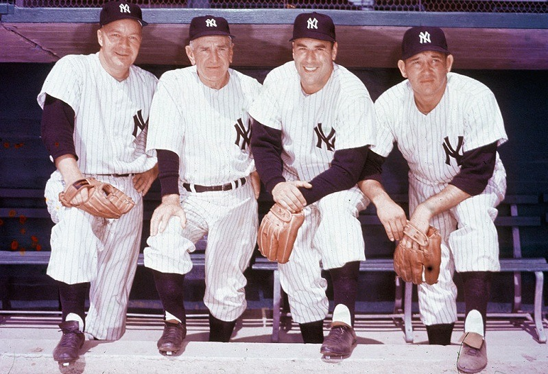 Four members of the New York Yankees baseball team pose in a dugout, 1950s. From left, pitcher Ed Lopat (1918 - 1992), manager Casey Stengel (1890 - 1975), pitcher Vic Raschi (1919 - 1988), and pitcher Allie Reynolds (1917 - 1994).