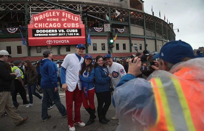 Exterior shot of Wrigley Field on Opening Night 2017 with fans posing in front of famous sign